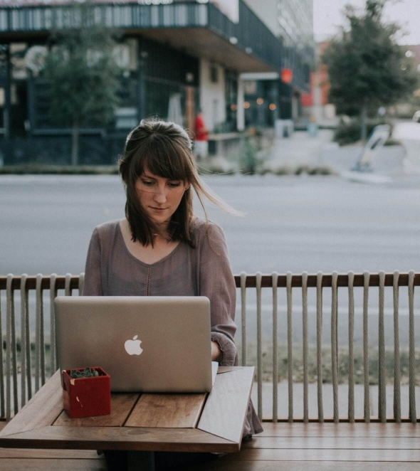 Woman sitting outside working on laptop